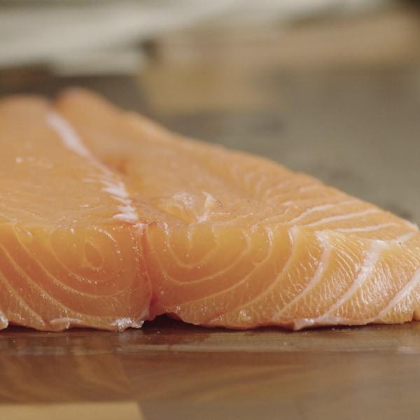 Un filet de saumon cru repose sur une planche à cuisiner.