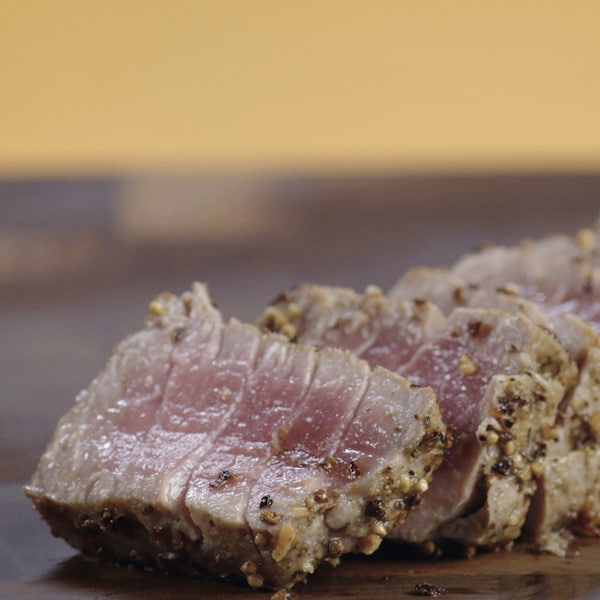 Un tataki de thon a été coupé en tranche sur une planche à découper.