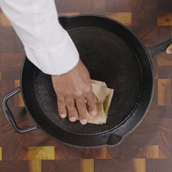 Une personne tient à la main une poêle en fonte et de l'autre essuie celle-ci avec un torchon en papier.