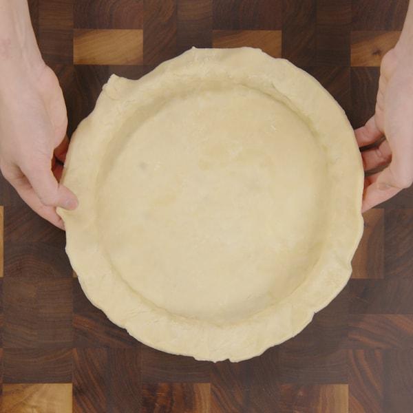 Une personne étend doucement de la pâte dans un moule à tartre.