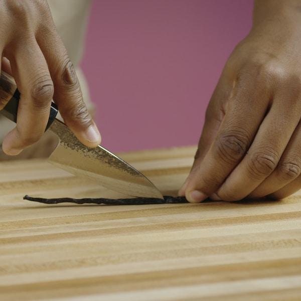 Au moyen d'un couteau, une personne coupe une gousse de vanille.