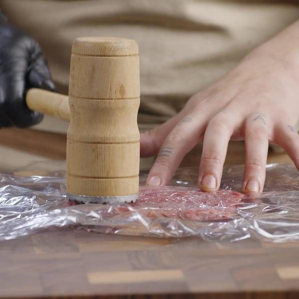 Une personne utilise le côté plat du maillet pour aplanir le morceau de viande sur une surface de travail.