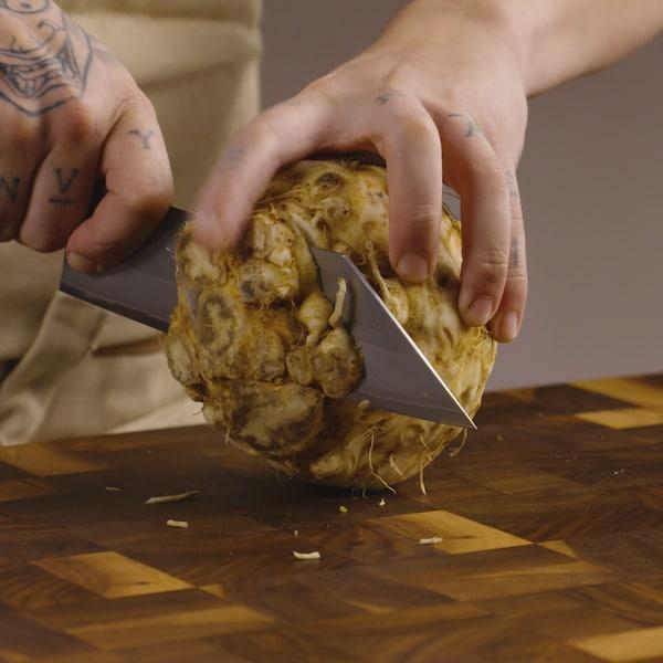 Une personne tient un couteau et coupe un céleri-rave sur un planche de travail.
