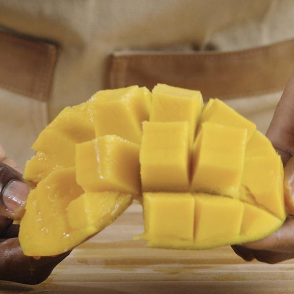 Une personne tient un morceau de mangue dans ses mains.
