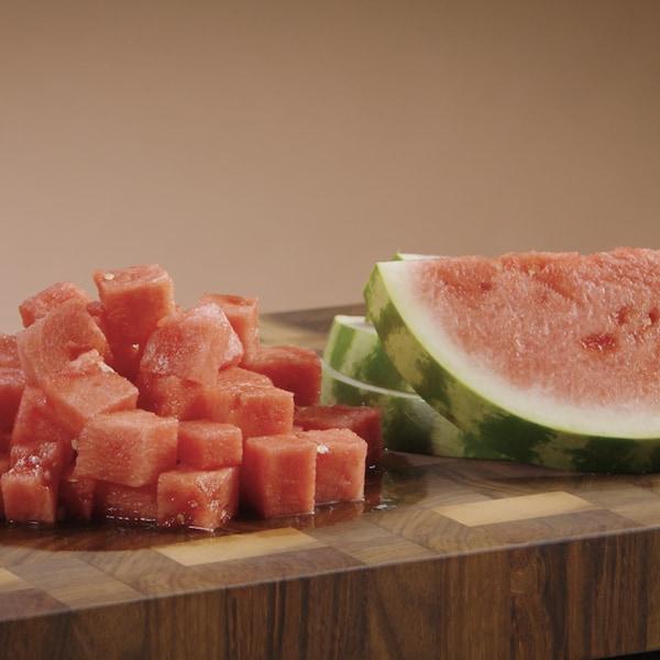 Un melon d'eau a été coupé en tranche et en cube. Les morceaux sont posés sur une table de travail.