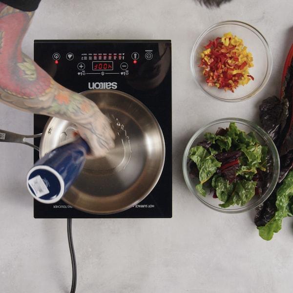 Une personne verse de l'huile d'olive dans un poêlon qui est sur une plaque à induction.