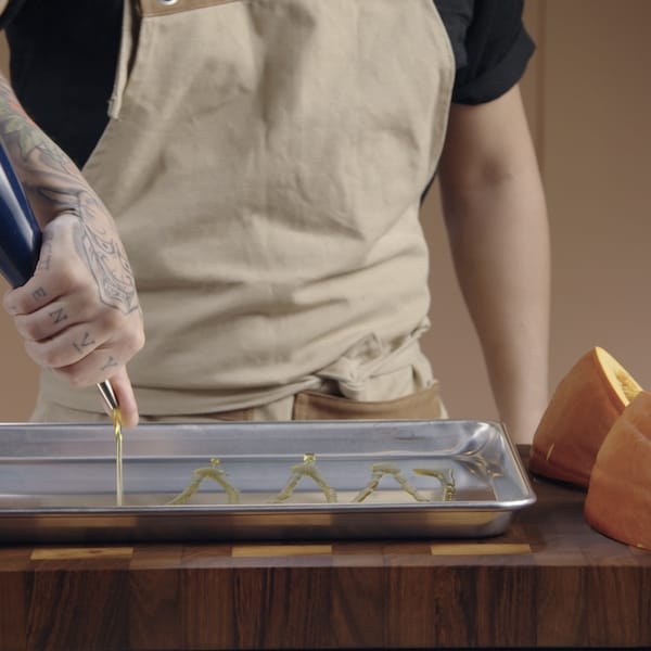 Une personne verse de l'huile d'olive sur une plaque de cuisson.