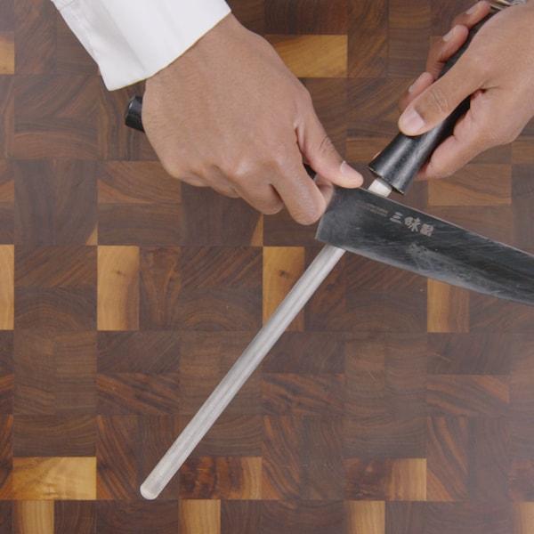 Une personne utilise un tige de métal ou de céramique permet de ramener la lame du couteau