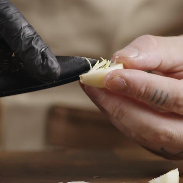 Couteau à la main, une personne retire le germe de l'ail.