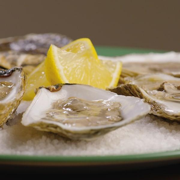 Dans assiette ronde, des quartiers de citrons et  des huîtres ouvertes ont été posés.