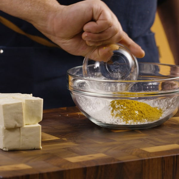 Une personne verse du cari dans un grand bol en verre.