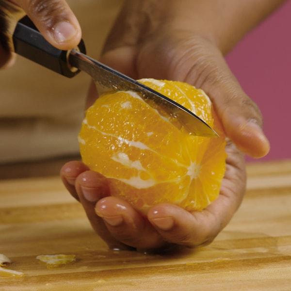 Une personne coupe entre chaque section de l'agrume.
