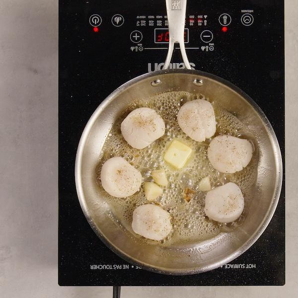 Des pétoncles cuisent dans une poêle.