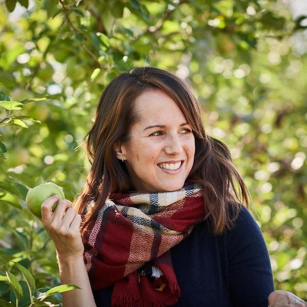 Geneviève O'Gleman se trouve dans un verger et tient une pomme croquée.