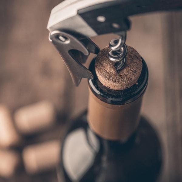 Une bouteille de vin avec un tire-bouchon.