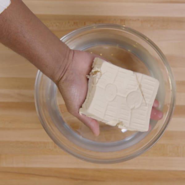 Une personne tient un bloc tofu fait maison. Il égoutte celui-ci au-dessus d'un bol en verre.