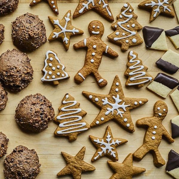 Biscuits de Noël de différentes tailles, formes et saveurs sur un plan de travail en bois.