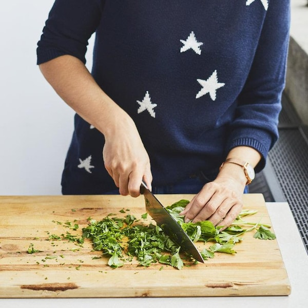 Une personne coupe du persil italien en utilisant un couteau de cuisine sur une planche à découper.