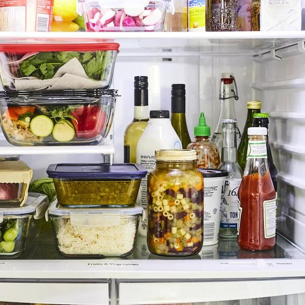 Sur l'étage du milieu d'un réfrigérateur, des ingrédients sont bien rangés et alignés. Les aliments solides sont placés à gauche et les aliments liquides sont placés à droite.