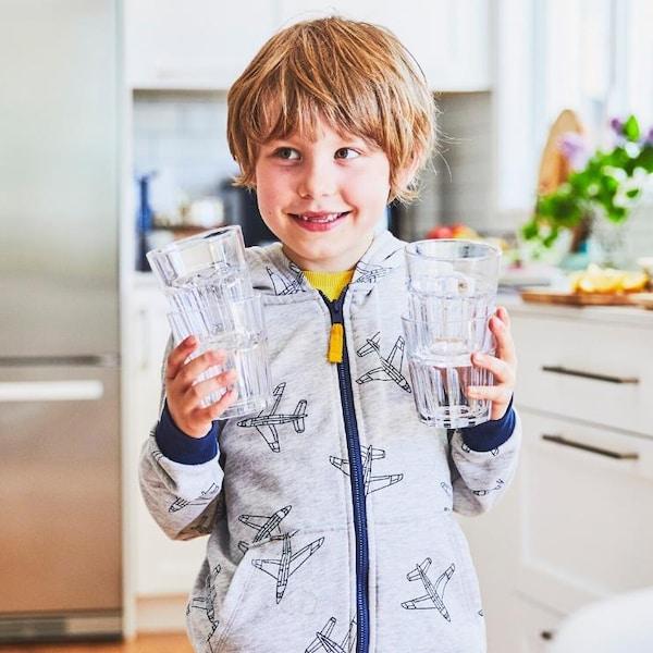 Garçon qui tient des verres vides dans ses mains.