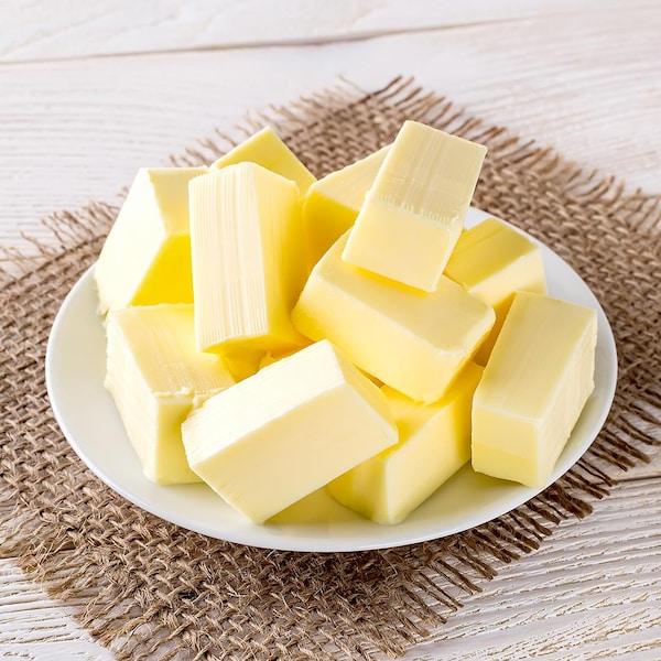 Des cubes de beurre servis dans une petite assiette.