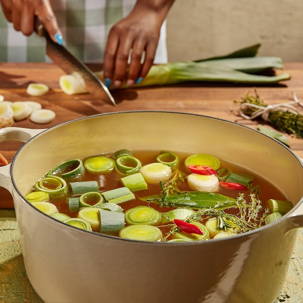 Une casserole remplie de bouillon avec des morceaux de poireaux qui flottent sur le dessus.