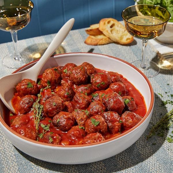Un grand plat rempli de boulettes de viande déposé sur une belle table avec des verres de vin.