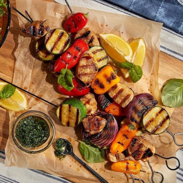 Quatre brochettes de porc avec des oignons, des poivrons et des courgettes.