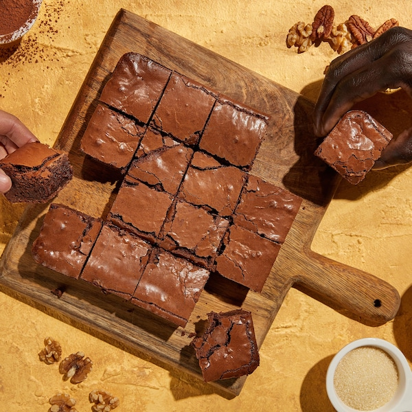 Un brownie coupé en morceaux sur une planche en bois.