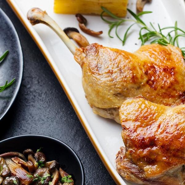 Des cuisses de canard rôties dans une assiette blanche.