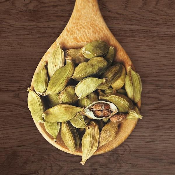 Plusieurs graines de cardamomes dans une cuillère en bois.
