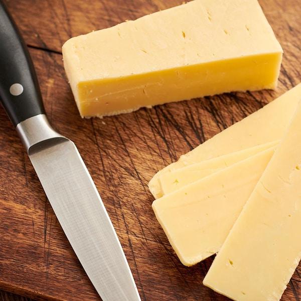 Un bloc de cheddar avec quelques tranches et un couteau.