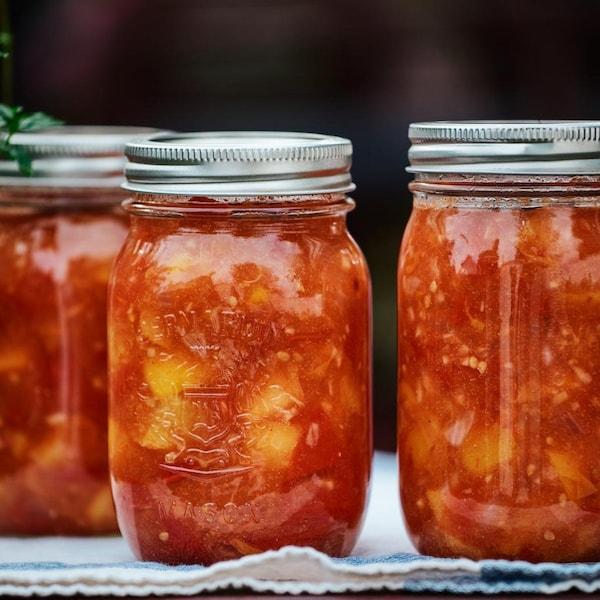 Des conserves de chutney aux tomates et aux pêches déposées sur un linge.
