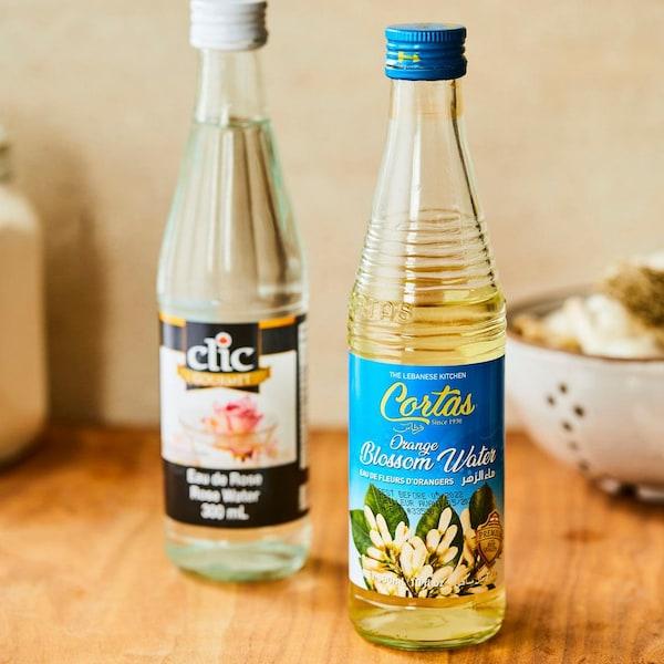 Deux bouteilles, une d'eau de rose et une d'eau de fleur d'oranger, sont déposées sur un comptoir de cuisine en bois.