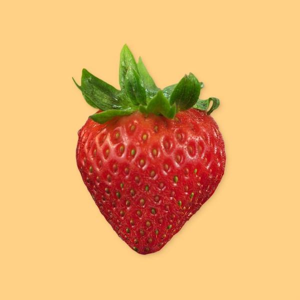 Une fraise sur un fond jaune.