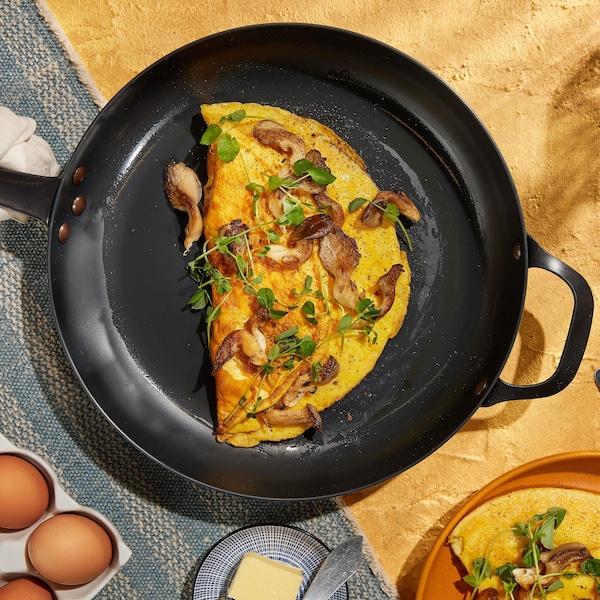 Une omelette recouverte de champignons et de verdure dans une poêle.