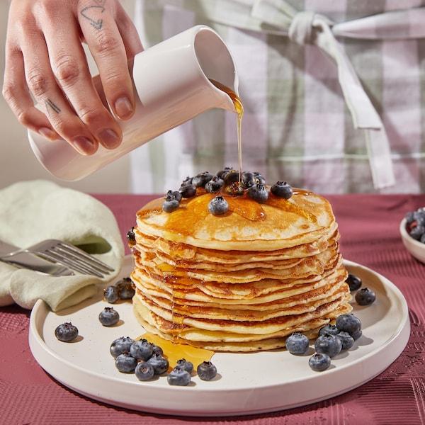 Une assiette avec une grosse pile de pancakes recouverts de bleuets et de sirop d'érable.