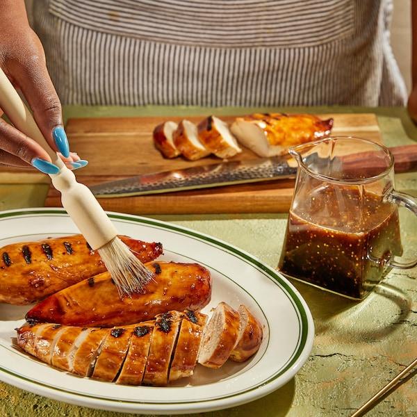 Des poitrines de poulet en train de se faire recouvrir de sauce.