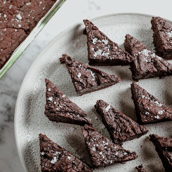 Une assiette de morceaux triangulaires de brownies, aux côtés d'une plaque de brownies.