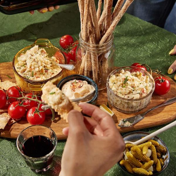 Une planche en bois recouverte de petites tomates en grappe, de petits craquelins, d'un bol de sauce et de deux bols de rillette.