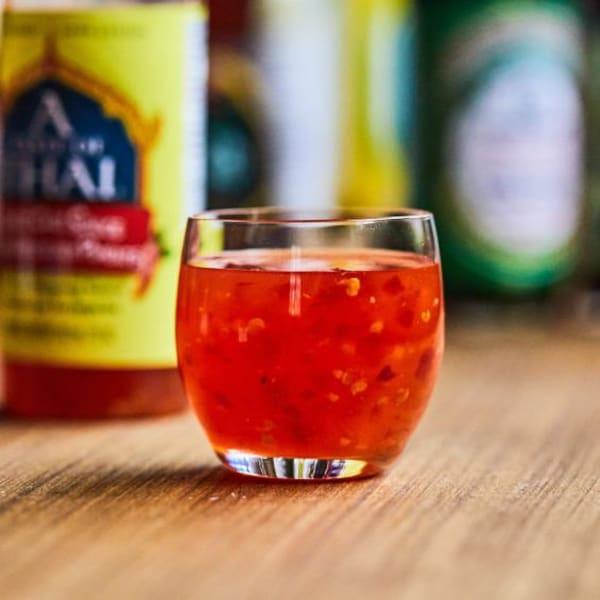 Un verre rempli de sauce chili thaïe sucrée.