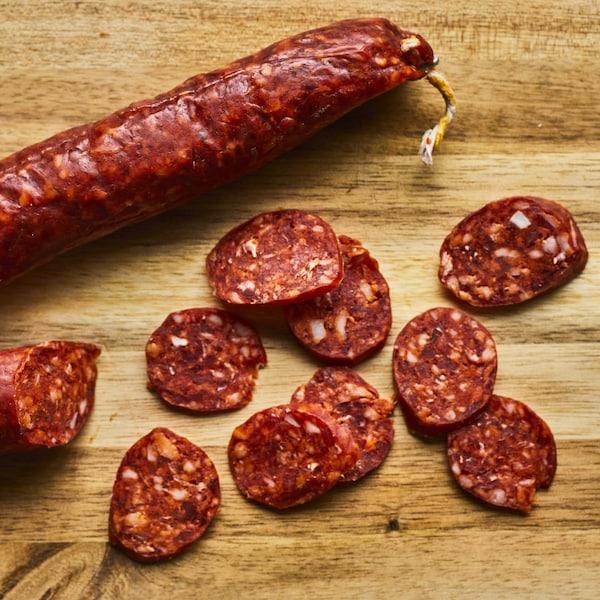 Saucisson chorizo coupé en partie avec des rondelles de chorizo sur une planche de bois.