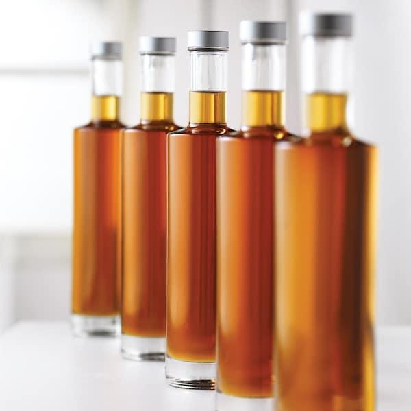 5 bouteilles en vitre remplies de sirop d'érable.