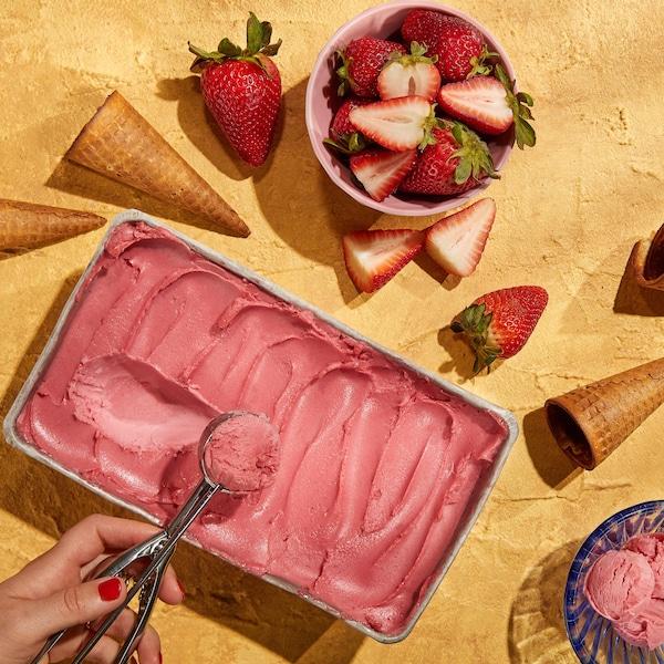 Un plat de sorbet aux fraises, des cornets et un bol de fraises fraîches.