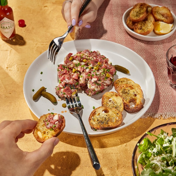 Du tartare de bœuf servi avec des croûtons et de petits cornichons.