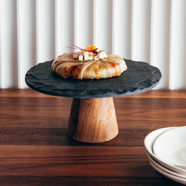 Une tarte Tatin garnie de cubes de fromage feta, sur un support à gâteau en ardoise et en bois.