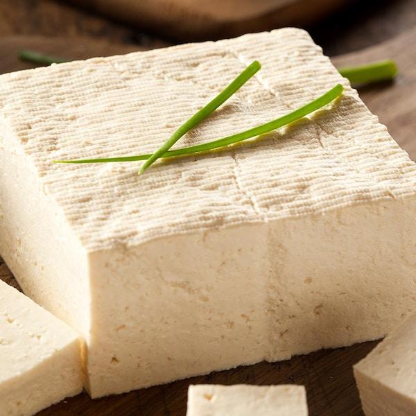 Un bloc de tofu tranché, garni de brins de ciboulette.