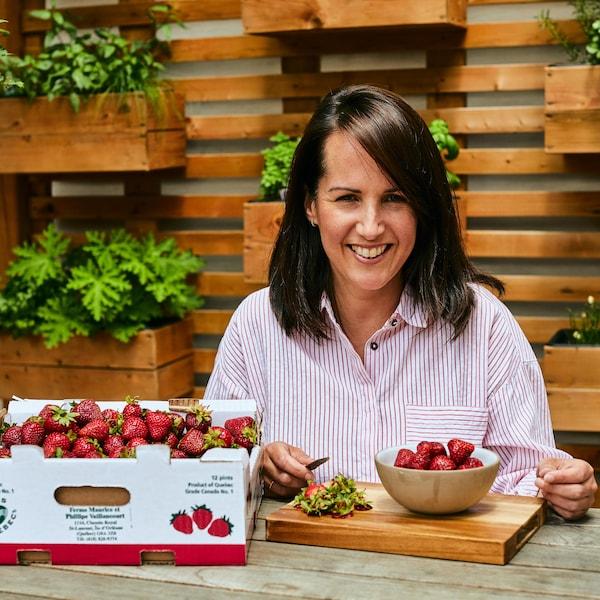 Geneviève O'Gleman est assise sur à une table à l'extérieur et elle équeute des fraises.
