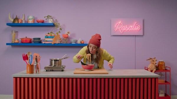 Rosalie tient entre des baguettes des nouilles ramen cuitent au-dessus d'un bol de soupe.