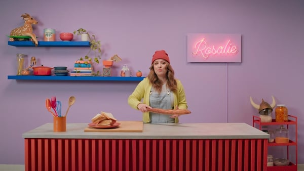 Rosalie tient dans ses mains une baguette de pain.